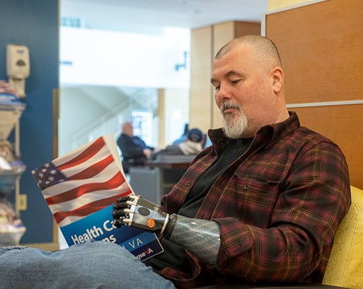 Veteran with a prosthetic arm reading.