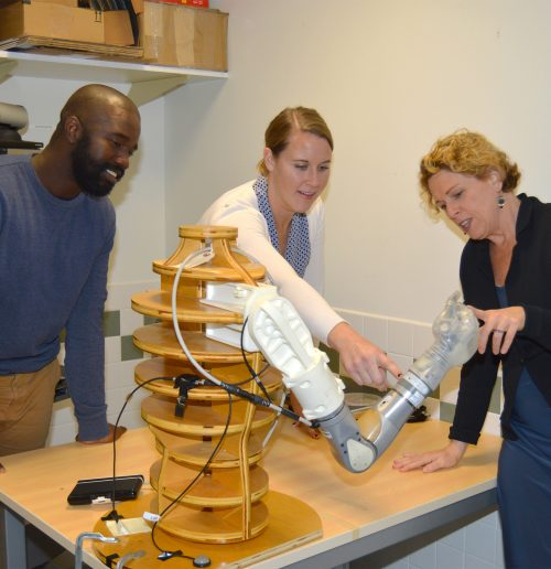 Researchers inspect prosthetic arm.